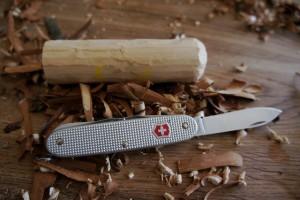 Wir schnitzen mit dem Taschenmesser die erste Kugel vom Schneemann. Foto (c) kinderoutdoor.de