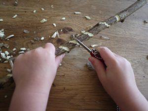Mit dem Taschenmesser schnitzen die Kinder nun Verzierungen in die Rinde.  foto (c) kinderoutdoor.de