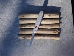 Kinder werken mit dem Taschenmesser ein Floß. Zuerst schneiden wie die Aststücke ab.  Foto (c) kinderoutdoor.de