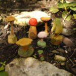 Kinder schnitzen einen Pilz mit dem Taschenmesser