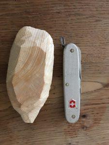 Kinder schnitzen mit dem Taschenmesser einen Faustkeil. Nein, auch wenn es so aussieht: Hier handelt es sich um ein Schwirrgerät, bevor die Feinarbeit losgeht. foto (c) kinderoutdoor.de