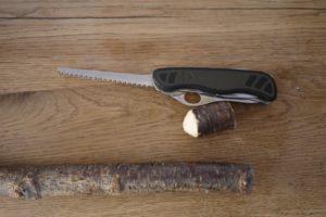 Kinder werken mit dem Taschenmesser und sägen das Stück Holz ab. foto (c) kinderoutdoor.de