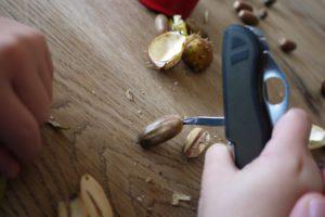 Kinder werken mit dem Taschenmesser und durchbohren die Eicheln mit der Ahle. foto (c) kinderoutdoor.de