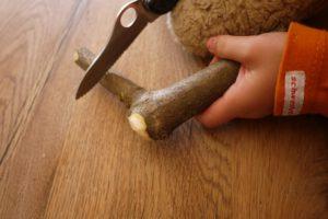 Mit dem Taschenmesser schnitzen die Kinder das Ende vom Astholz rund ab.  foto (c) kinderoutdoor.de
