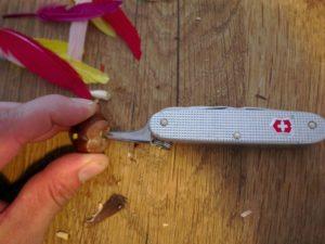 Kinder werken mit dem Taschenmesser und durchbohren die Kastanie mittig. (c) kinderoutdoor.de