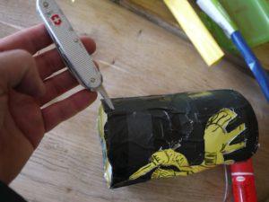 Mit dem Taschenmesser bohren die Kinder zwei Löcher für den Draht in die Kakaodose. foto (c) kinderoutdoor.de