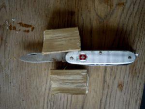Outdoorkids werken mit dem Taschenmesser und spalten das Astholz in der Mitte. foto (c) kinderoutdoor.de