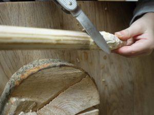 Mit dem Taschenmesser schnitzen die Kinder ein Ende vom Ast spitz an.  foto (c) kinderoutdoor.de