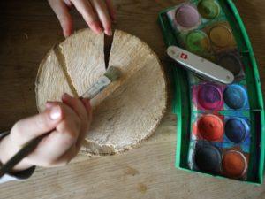 Kinder werken mit dem Taschenmesser: Eine kurze Pause vom Schnitzen und den Hut vom Fliegenpilz anmalen.  foto (c) kinderoutdoor.de