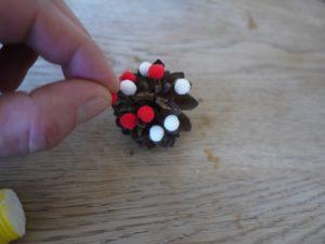 Kinder basteln Weihnachtsschmuck und kleben die Pompons am Kiefernzapfen an.  foto (c) kinderoutdoor.de