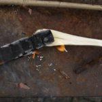 Kinder schnitzen einen Holzlöffel mit Hilfe vom Lagerfeuer