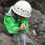 Kinder am Klettersteig im Herbst: Die Familie ist im Felsen unterwegs