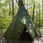 Kinder und Eltern bauen ein Zelt im Wald: Wir haben die Bauanleitung dazu